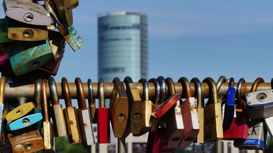 Close-up of padlocks hanging on metal against sky