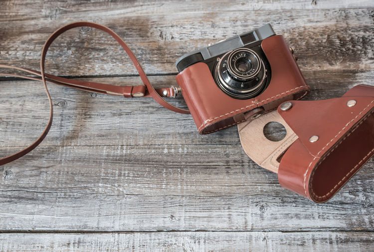 High angle view of antique camera with cover on table