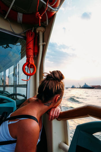 young woman looking out on boat trip Venice Venice, Italy Italy Travel Travel Destinations Real People Leisure Activity One Person Lifestyles Transportation Water Sky Vehicle Interior Mode Of Transportation Nature Day Nautical Vessel Rear View Sea Adult Women Outdoors Sunset Golden Hour Boat