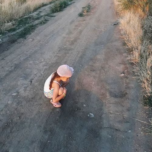 High angle view of girl sitting in hat on road.