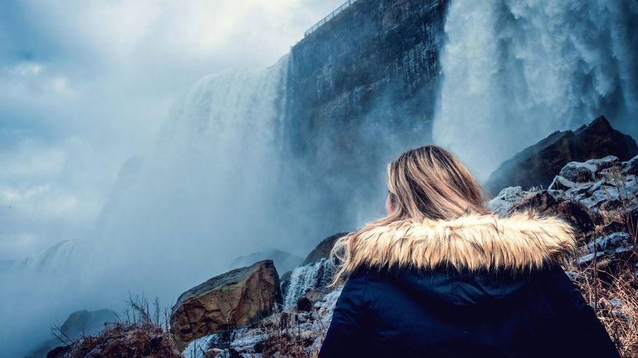 Rear view of woman wearing fur coat standing against waterfall