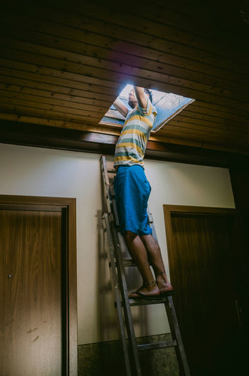 Full Length Of Man Standing On Ladder At Home