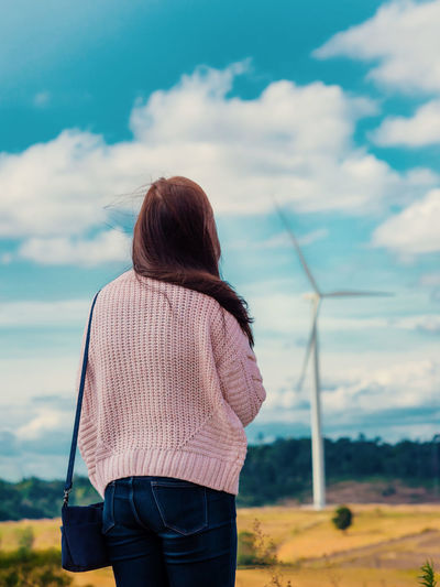 Rear view of woman standing against windmill on landscape