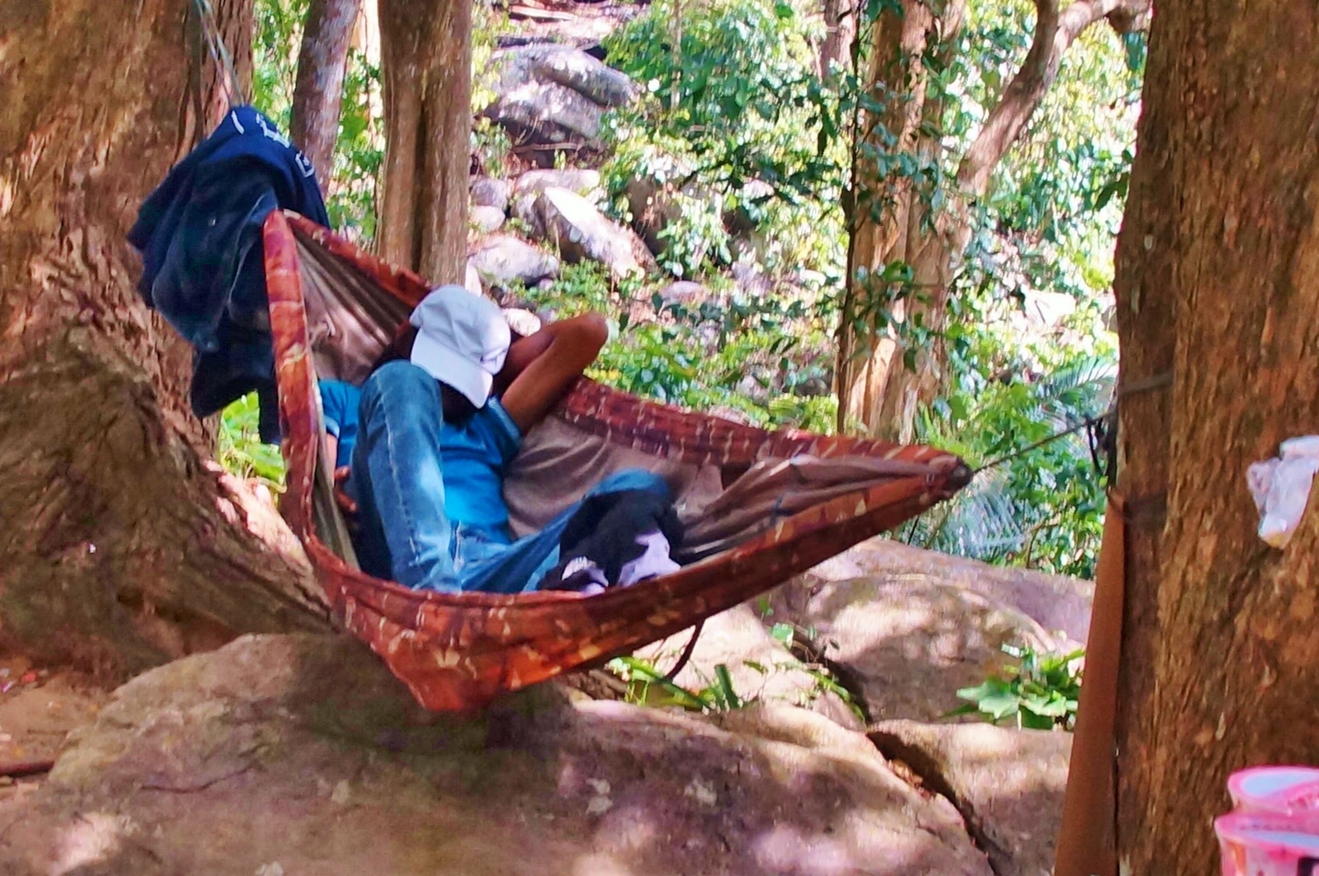 LOW SECTION OF MAN RELAXING ON HAMMOCK