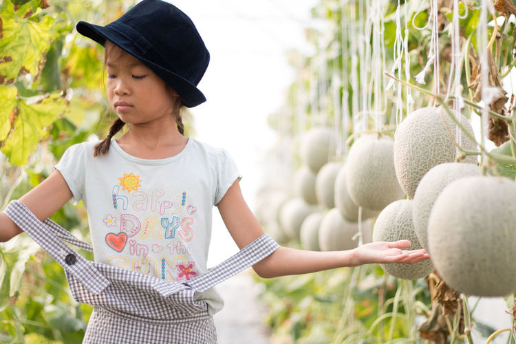 Girl wearing hat while standing by plants with fruits in farm