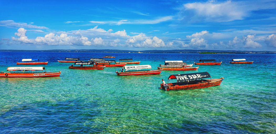 Boats moored in sea against blue sky