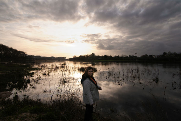 Woman standing on lake against sky during sunset