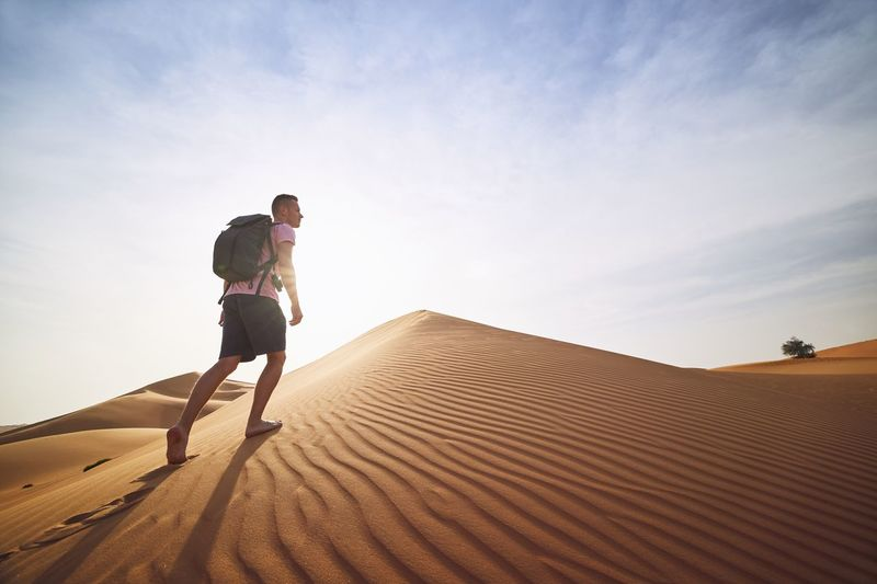 Low angle view of man walking on sand dunes at desert against sky