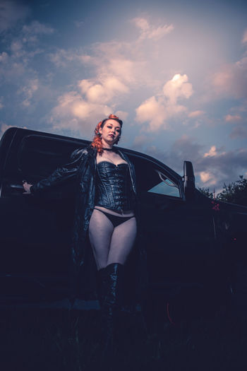 Portrait of woman standing by car against sky