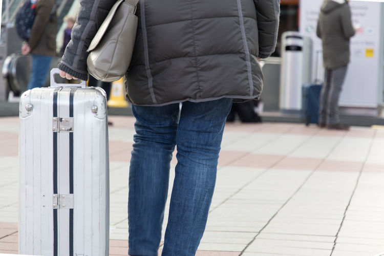 Rear view midsection of woman with luggage standing on tiled floor