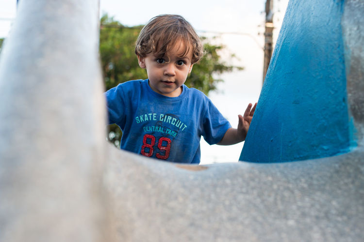 Low angle portrait of boy playing on slide at playground