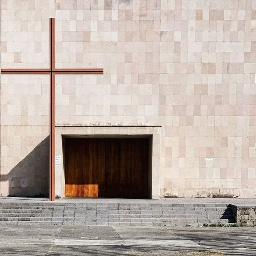 Religious cross on footpath against wall of building