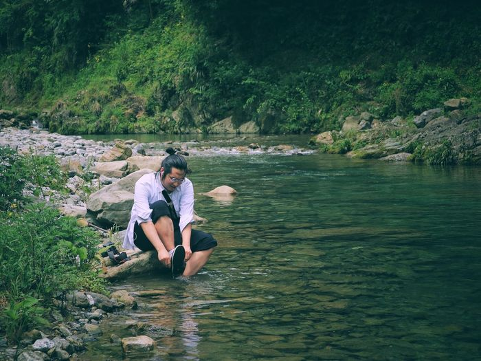 Man removing shoe while sitting on rock by stream