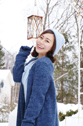 Portrait of smiling young woman standing in snow