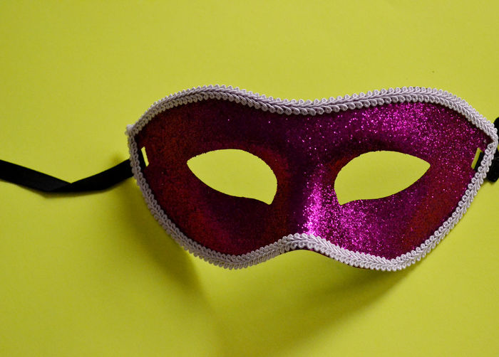 Close-up of pink mask on yellow background