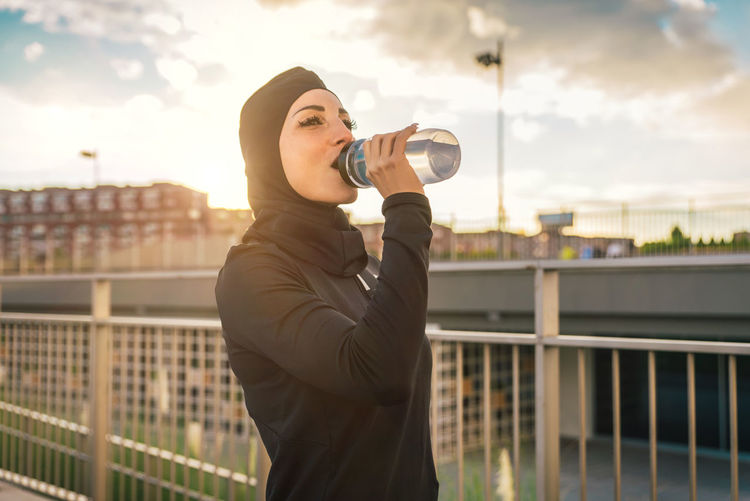 Beautiful woman wearing hijab drinking water against building during sunrise