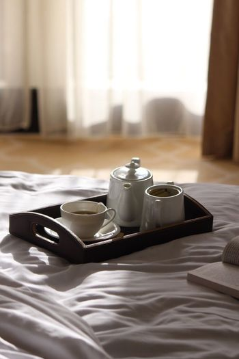 Cup With Kettle In Serving Tray On Bed At Home