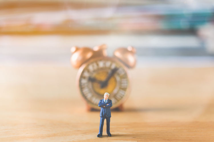 Close-Up Of Figurine Against Clock On Table