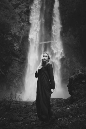 Full length of young woman standing on rock against waterfall