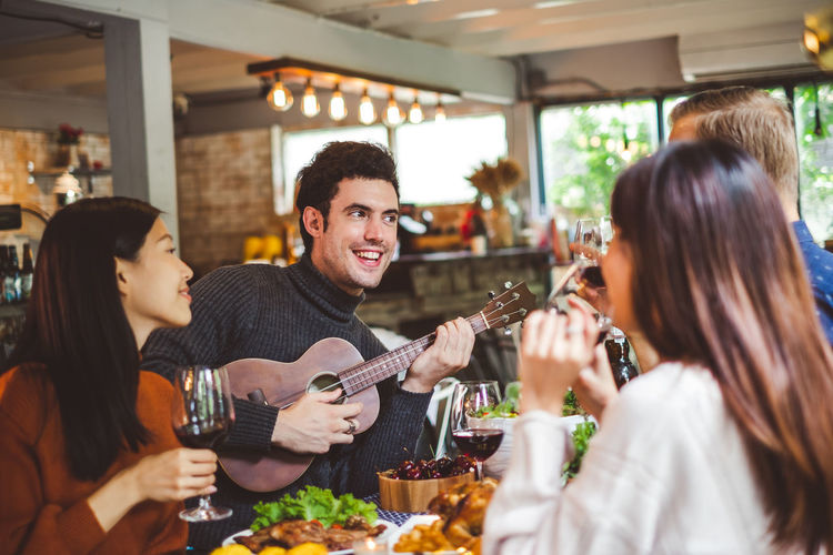 Man Playing Guitar With Friends At Restaurant