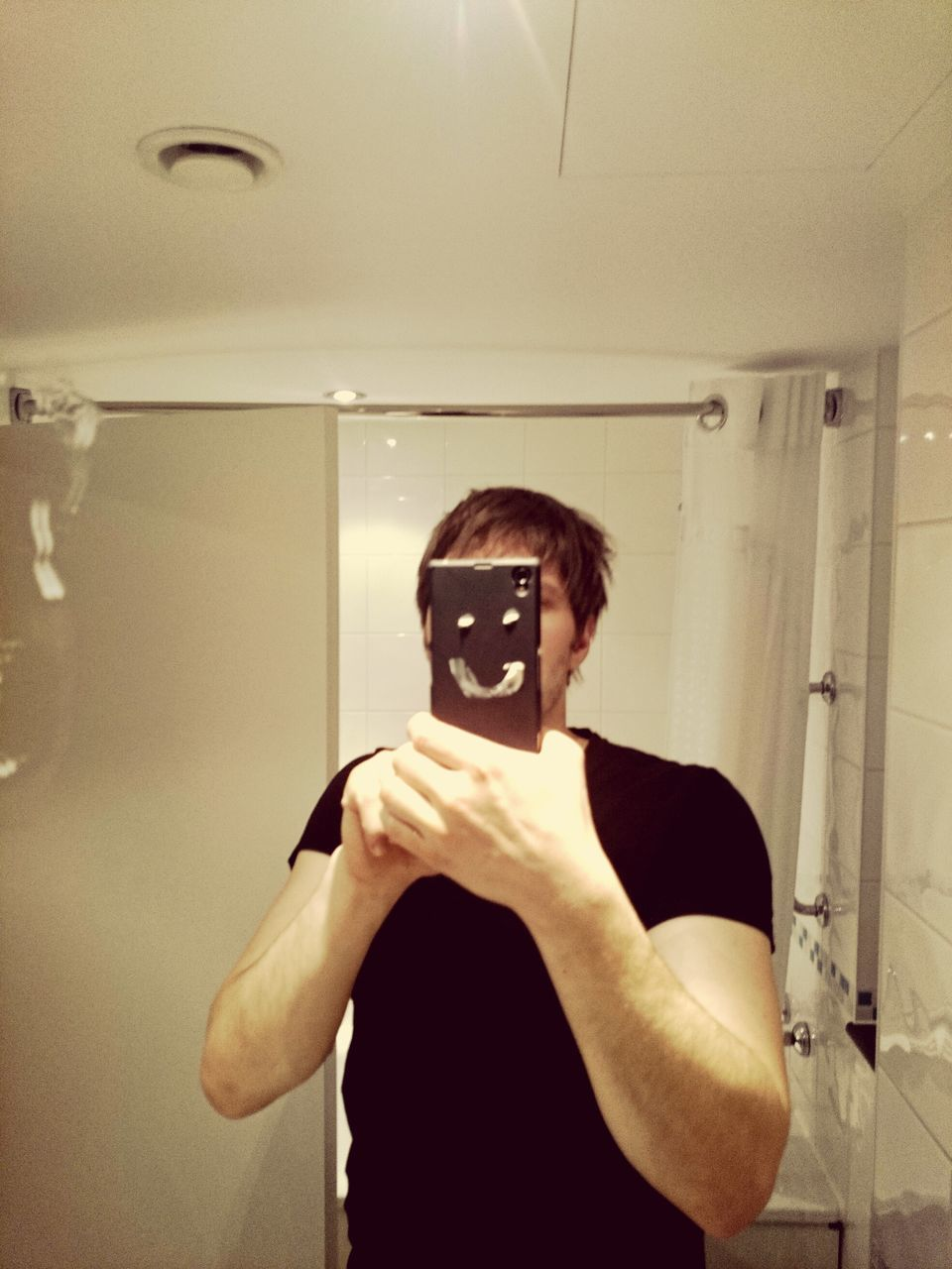 Man Holding Smart Phone With Smiley Face While Standing In Bathroom