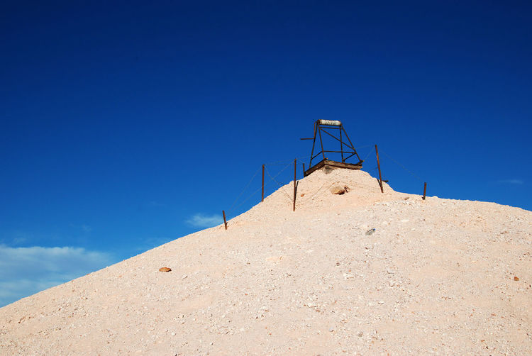 Low angle view of built structure on sand against blue sky