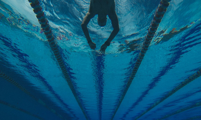 Low angle view of man swimming in pool