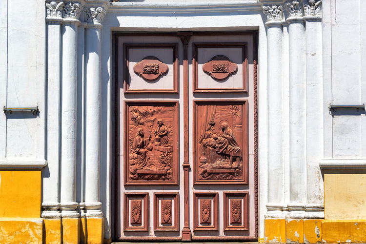 Entrance of san sebastian church in city on sunny day