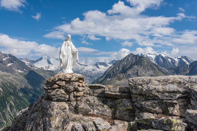 White statue of virgin mary, mother of god, placed on top of the mountains, blue sky, white clouds.