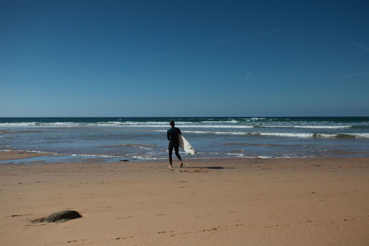 Man with surfboard at beach on sunny day