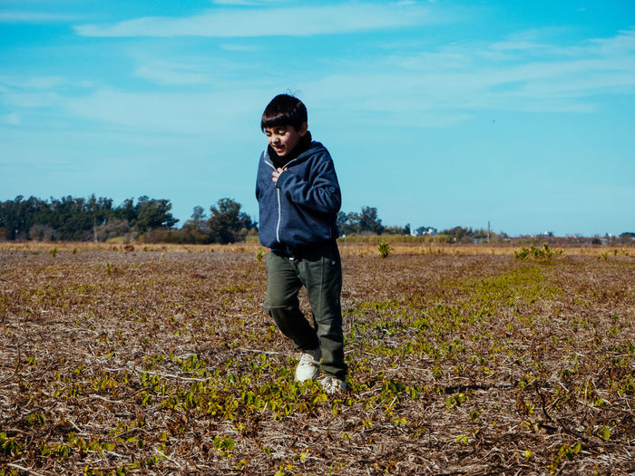 Boy running on land against sky