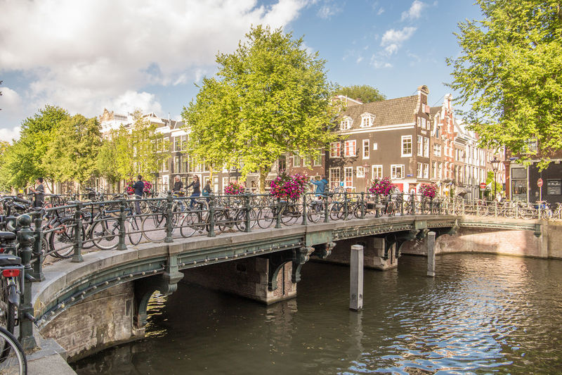Amsterdam Netherlands Architectural Column Architecture Bridge Bridge - Man Made Structure Building Building Exterior Built Structure Canal Houses City Cloud - Sky Connection Day Dutch Architecture Dutch Houses Group Of People Herengracht Holland Nature Outdoors Plant River Sky Tourism Travel Destinations Tree Water
