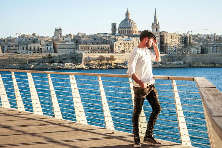 Full Length Of Man Standing On Railing On Footbridge Over River
