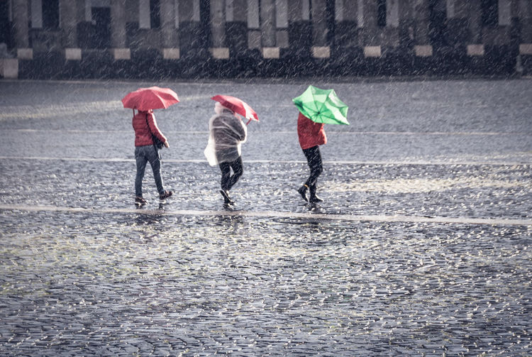 People walking on wet road during rainy season