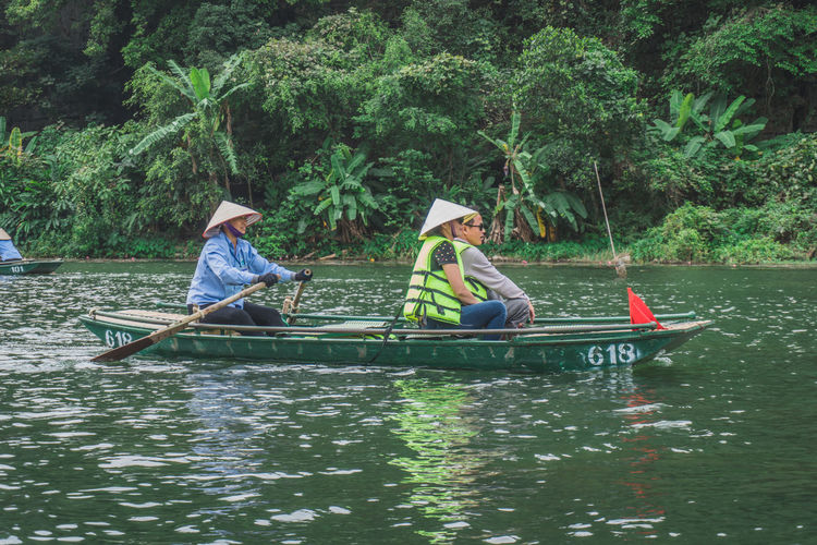 Men sitting on boat in river against trees