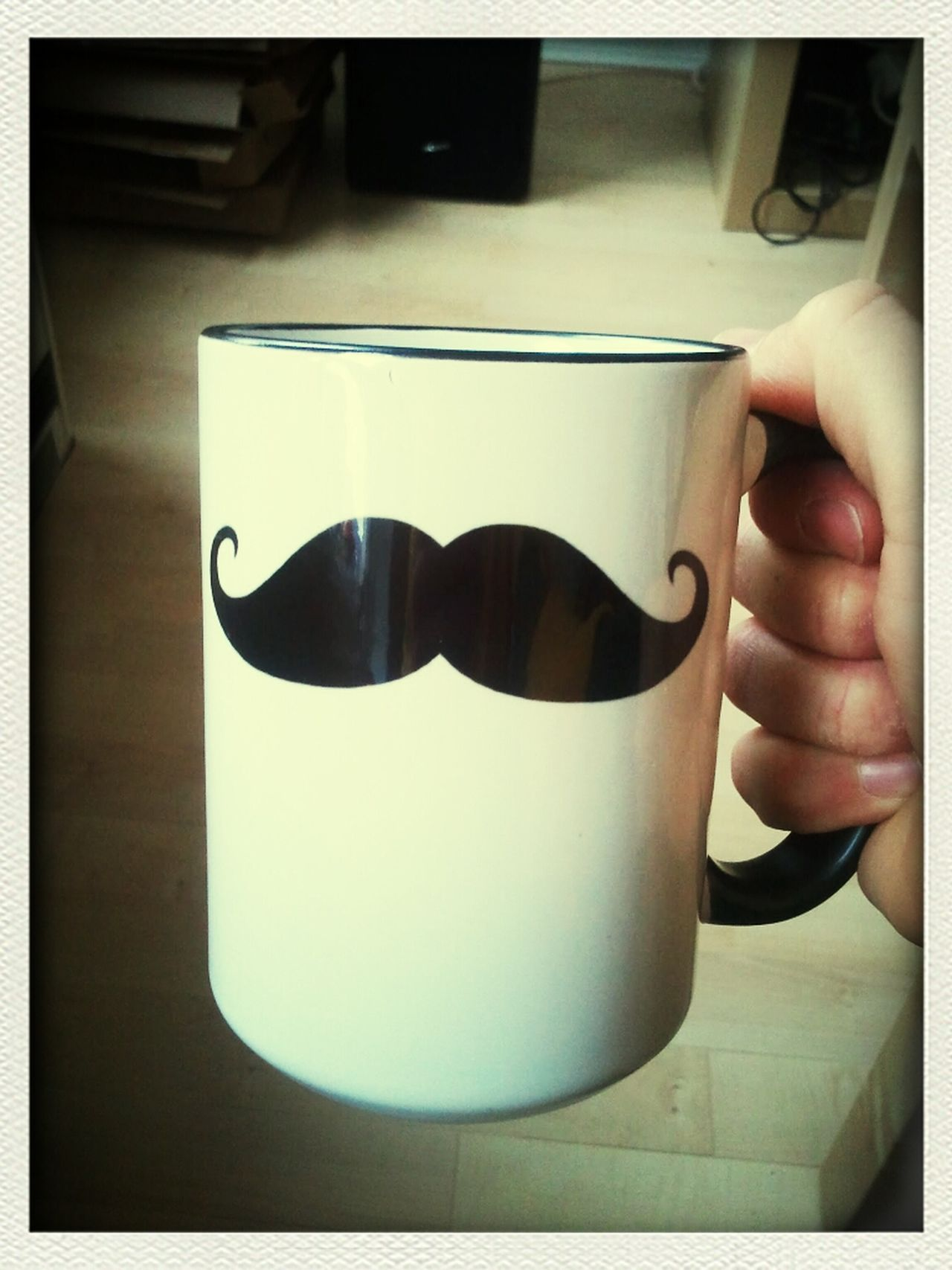 Cropped image of hand holding coffee cup with mustache