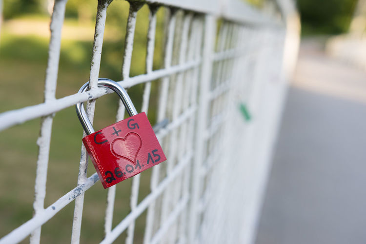 Close-up of love padlocks hanging on fence
