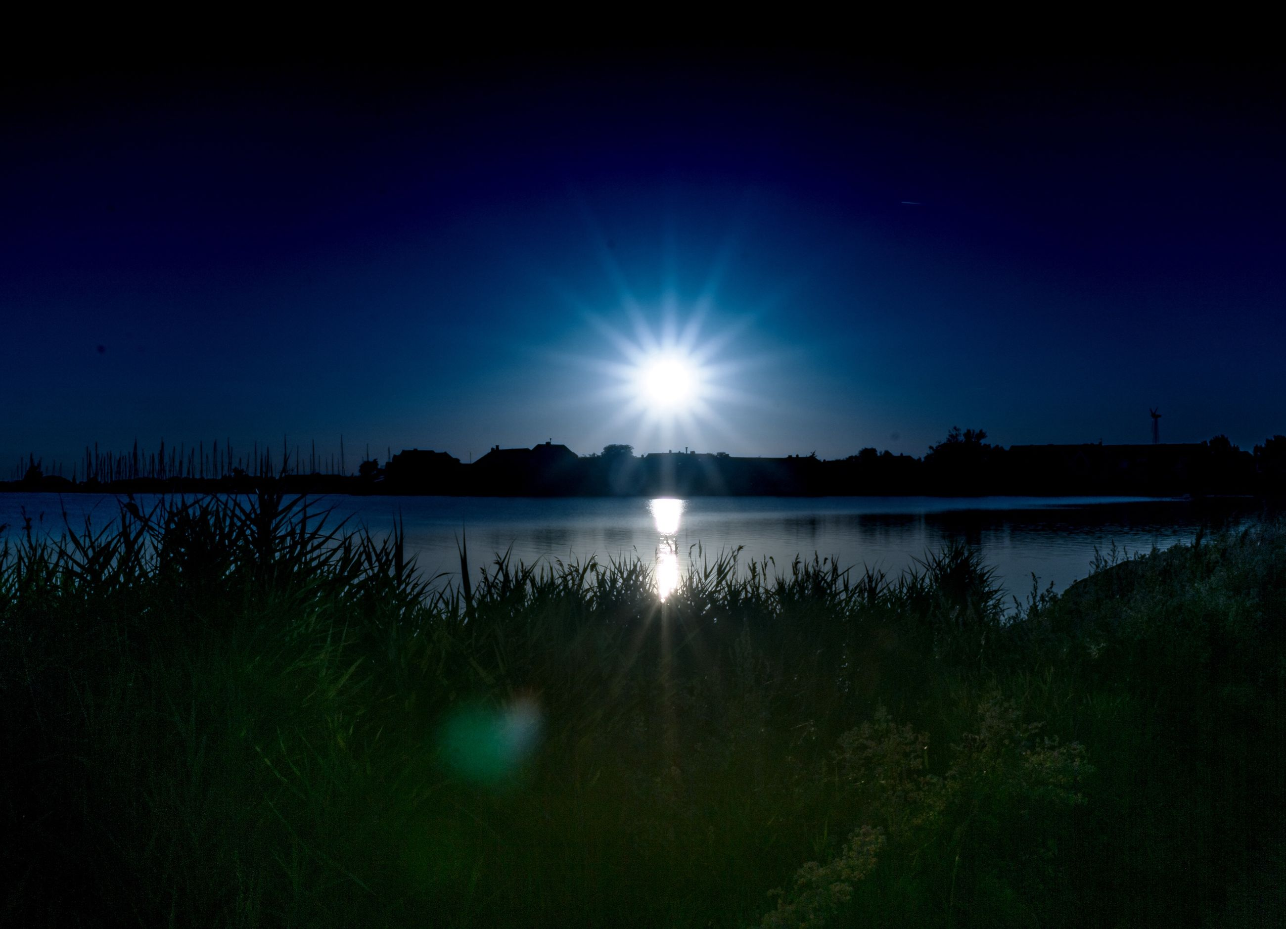 sky, water, scenics - nature, tranquility, beauty in nature, tranquil scene, plant, lake, tree, reflection, nature, no people, lens flare, sun, blue, non-urban scene, idyllic, sunlight, silhouette, outdoors, moonlight