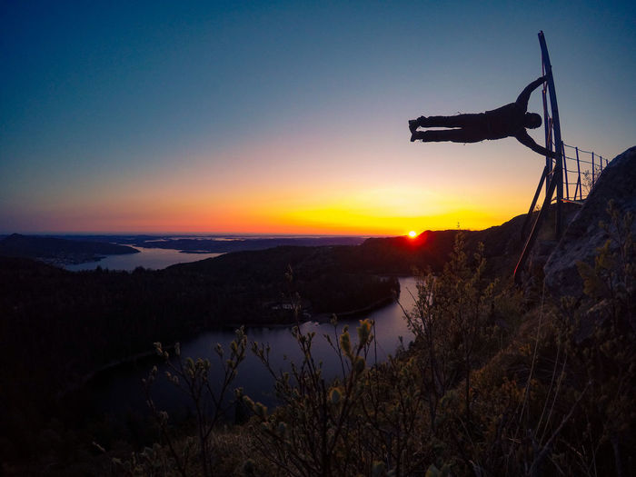 Silhouette Man Doing Yoga By Holding Railing On Cliff At Sunset