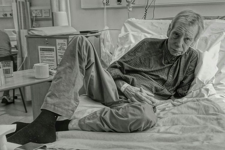 Portrait of senior man reclining on bed at hospital
