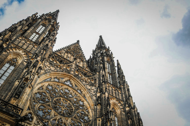 Low angle view of st vitus cathedral against cloudy sky