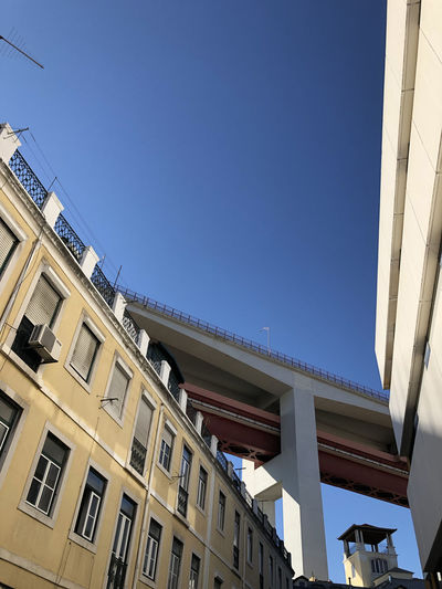 Low angle view of bridge over residential neighbourhood in Lisbon, Portugal Lisbon Portugal Architecture Building Exterior Built Structure Low Angle View Building Sky Day Nature No People Sunlight Clear Sky Residential District City Outdoors Window Blue Balcony Copy Space House Apartment