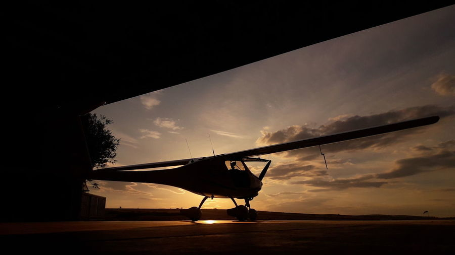 Silhouette airplane on airport runway against sky during sunset