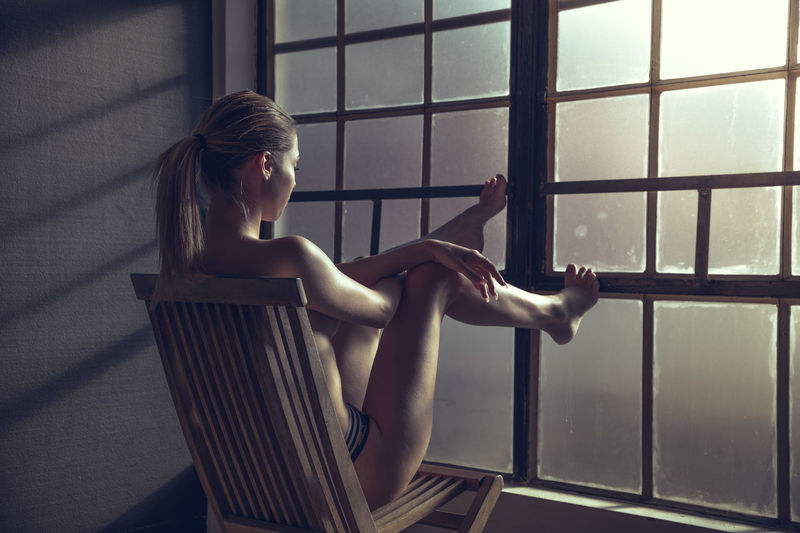 Full length of sensuous woman sitting on chair by window