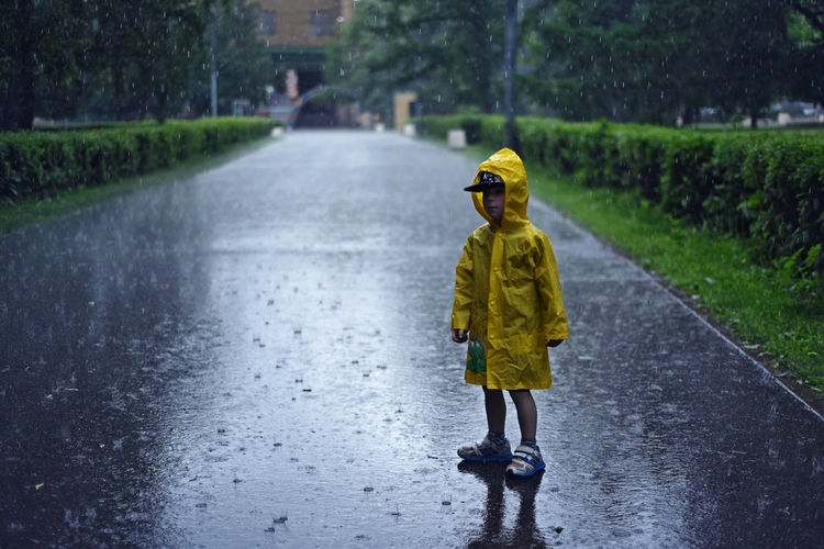 Full Length Of Boy In Yellow Raincoat