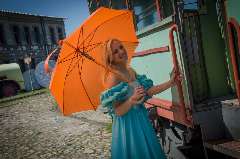 Woman With Umbrella Standing By Old-Fashioned Tram