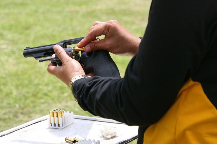 Cropped Image Of Man Loading Bullets In Gun
