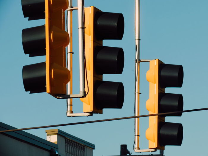 Low angle view of traffic lights against blue sky