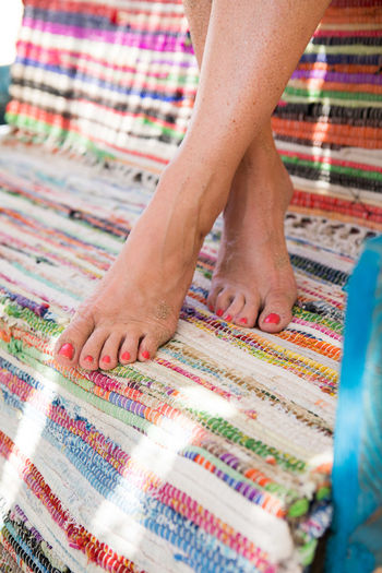Low section of womans feet on a multi colored carpet