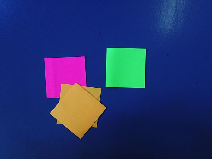 Close-Up Of Sticky Notes On Blue Wall